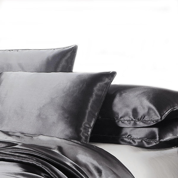 black satin silk feel pillowcase set on a bed with a white background