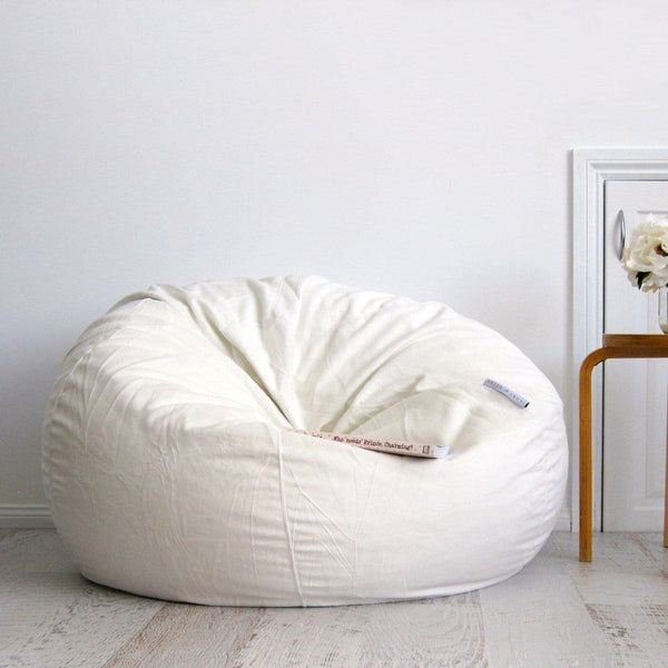 ivory fur beanbag on wooden floor with book resting on it
