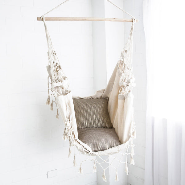 cream hanging hammock chair with cushions next to window
