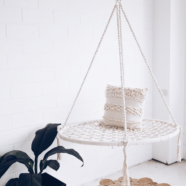 cream nest swing with pillow and hanging next to a plant