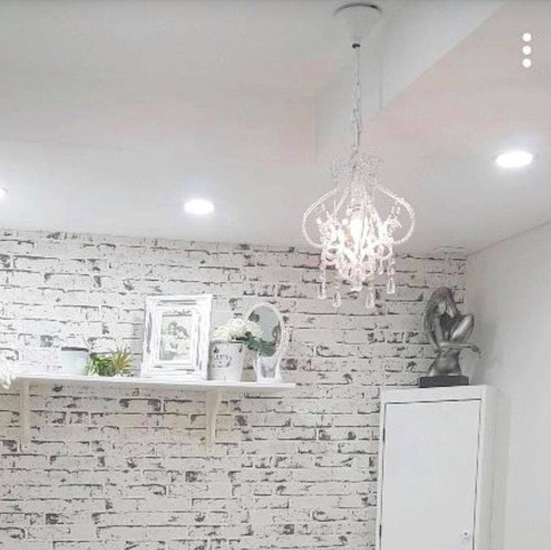white darling chandelier hanging in a living area with a brick wallpaper background