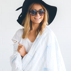 girl wrapped up in a midsummer dream round beach towel wearing an hat and sunglasses