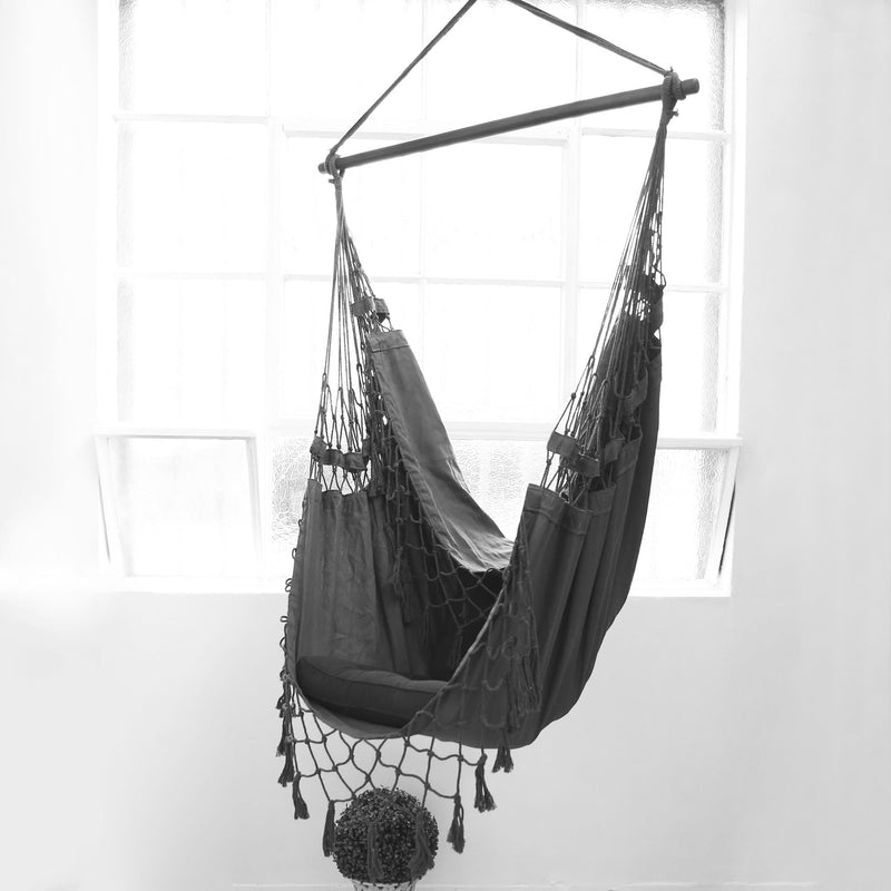 grey hanging hammock chair with an industrial window behind