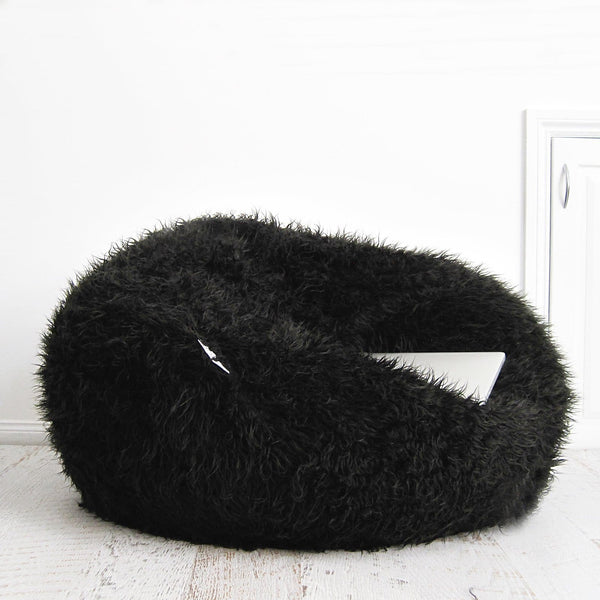 large black shaggy fur bean bag on wooden floor in front of white bricks