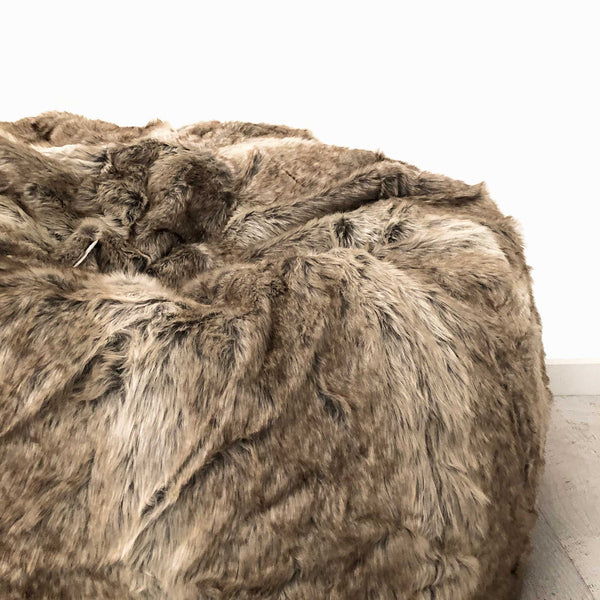 closeup of large lush fur beanbag on a wooden floor with a white background