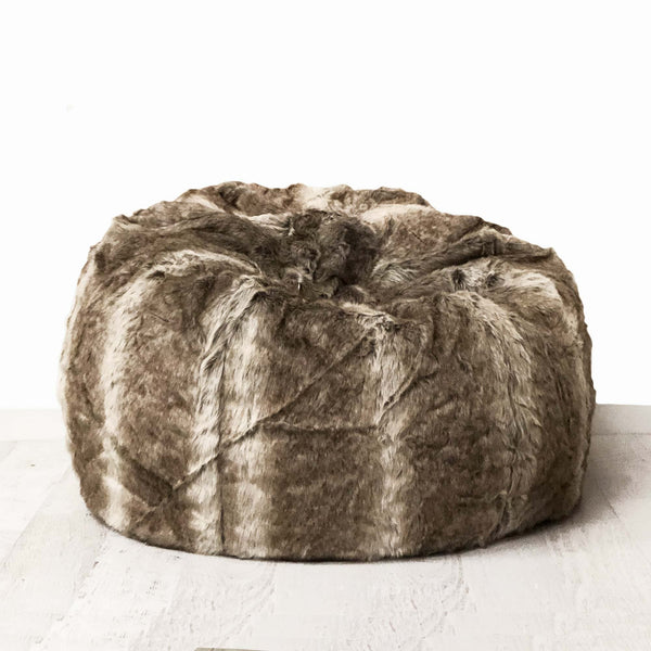 large lush fur beanbag on a wooden floor with a white background