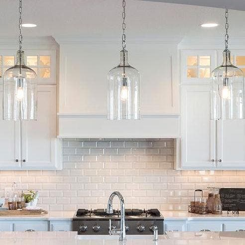 two glass jug pendants in a bright kitchen with vintage edison globe