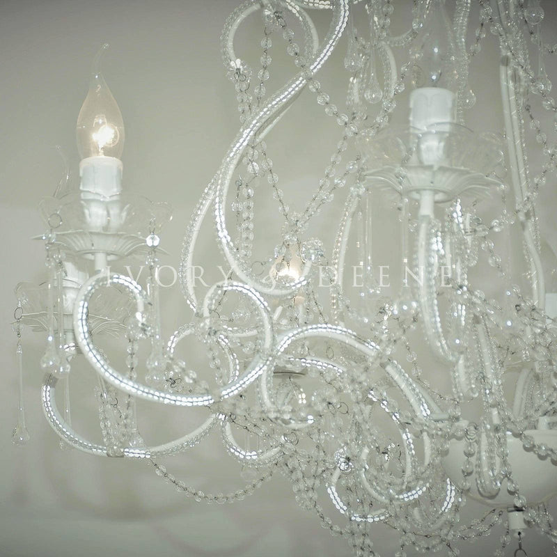 close up photo of a large french provincial cream chandelier in bedroom