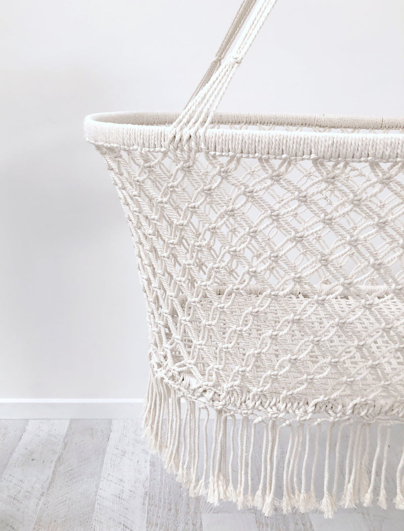 closeup of a handmade white macrame bassinet crib suitable to use with a dockatot