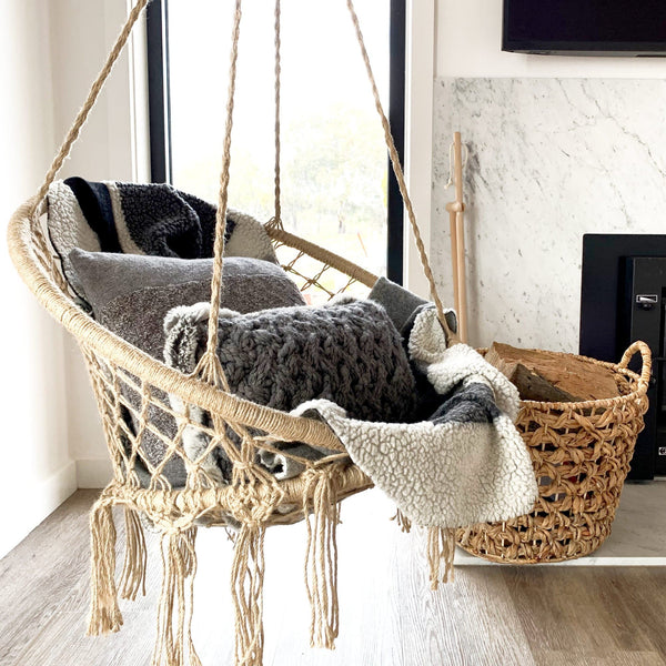 natural rope hanging macrame hammock chair with cushions and a cosy blanket