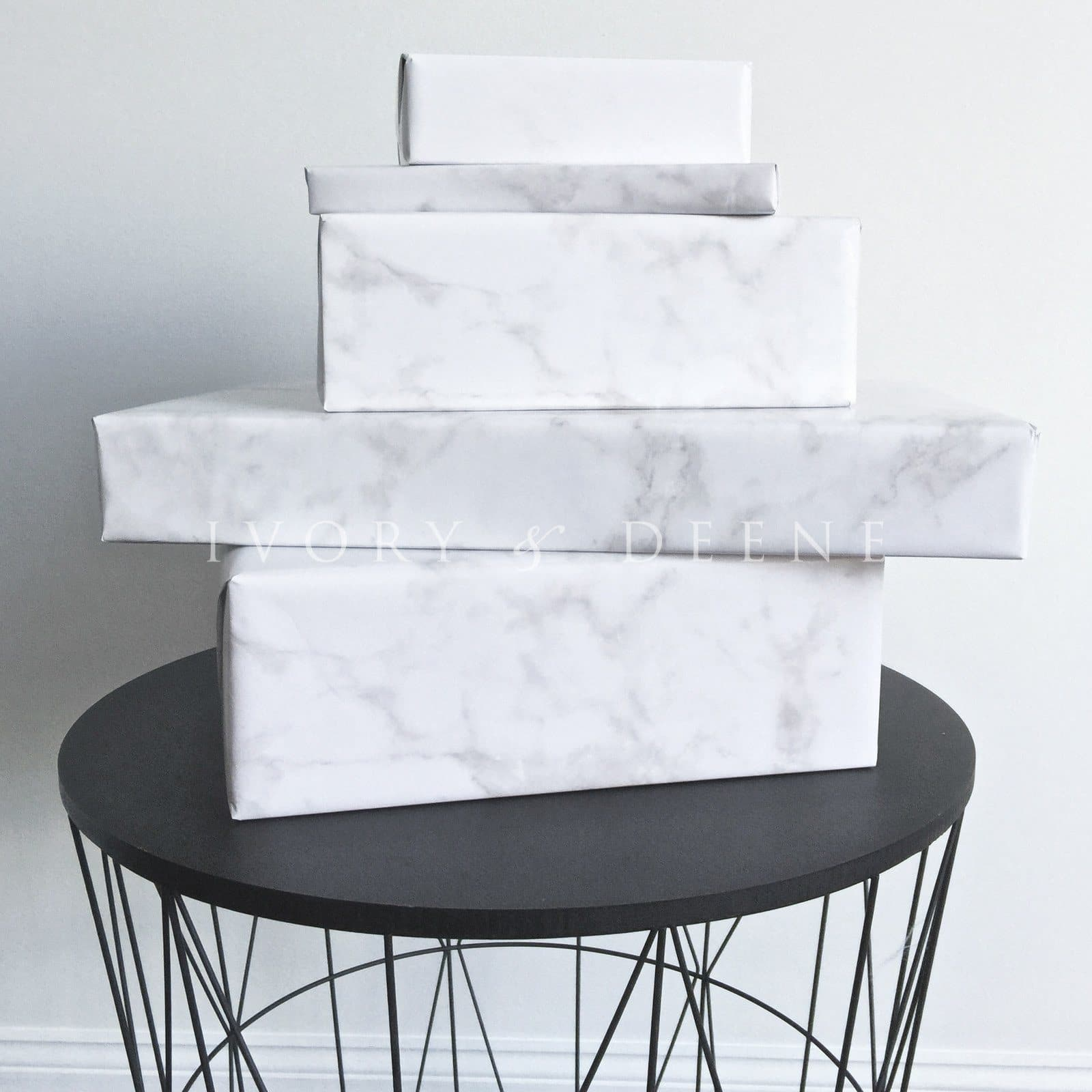 white marble wrapping paper gift wrap packages on a black modern wire side table