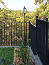 black metal lamp post installed in a garden next to an metal fence