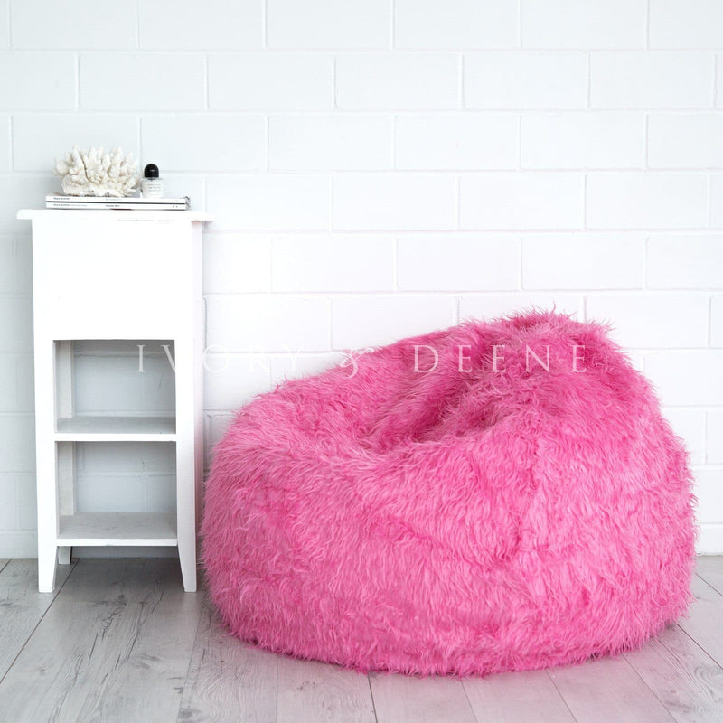 pink fur bean bag on wooden floor against white brick background and table with coral