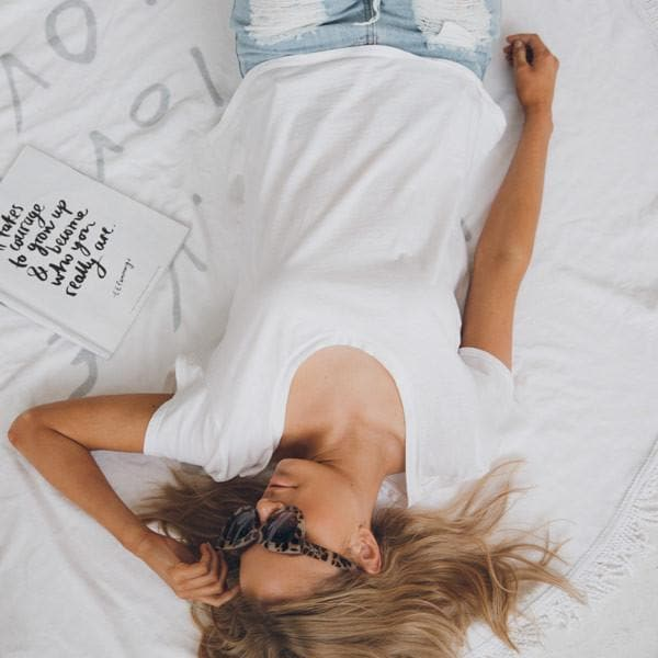girl laying on white love round towel wearing sunglasses with a book