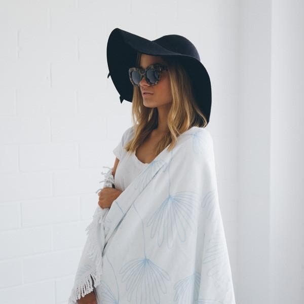 girl wrapped up in a midsummer dream round towel wearing an hat and sunglasses