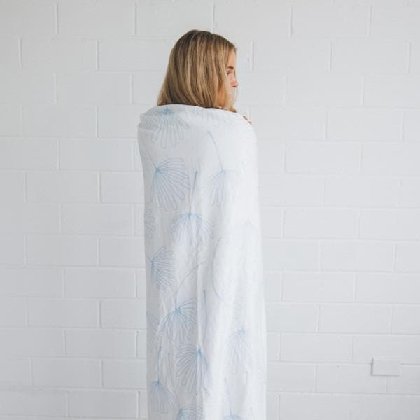 girl wrapped in midsummer dream towel standing against a white brick wall