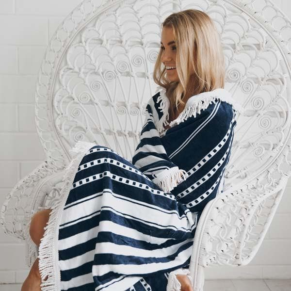 girl wrapped up in oceans blue and white round towel sitting on cane fan chair