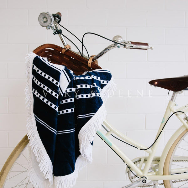 round beach towel sitting in vintage bike basket