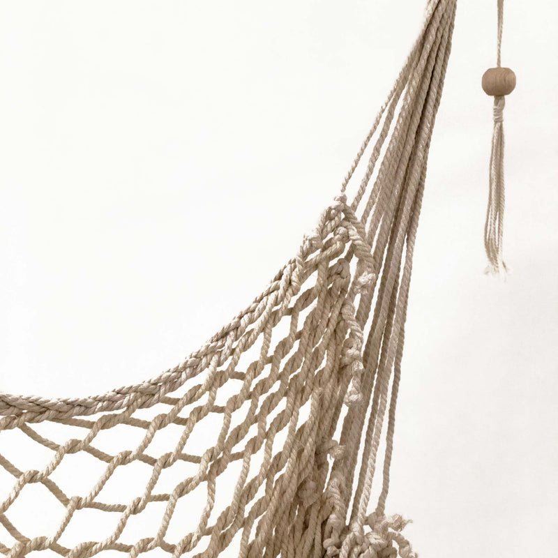 cream macrame rope hammock swing with wooden beads on a white background