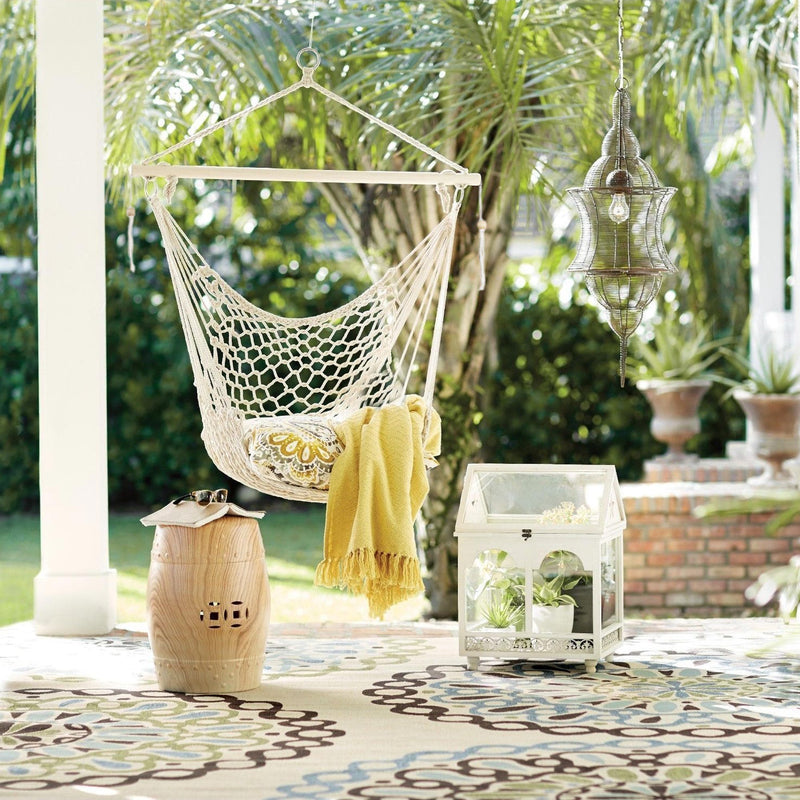 macrame hammock hanging outside with cushion and blanket