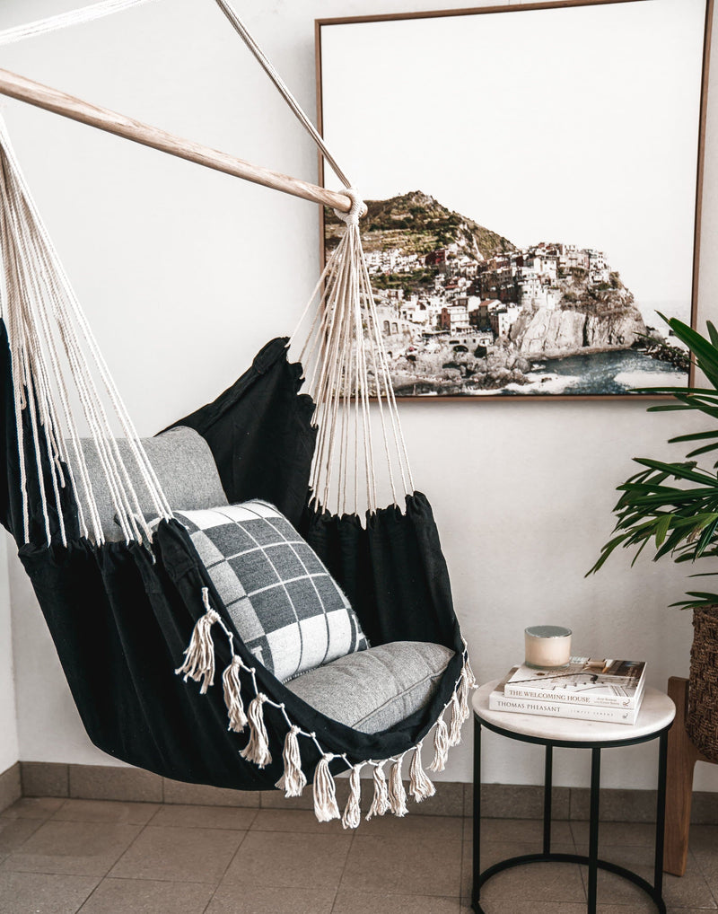 black soho hanging hammock chair with natural fringe detail outside lifestyle image