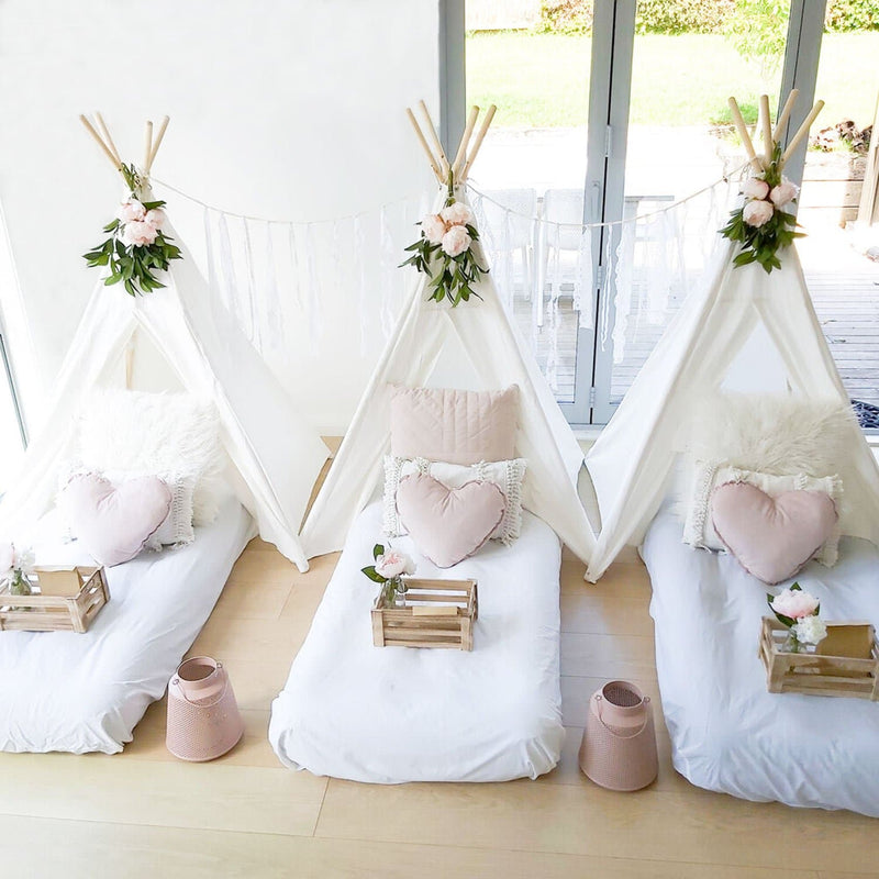 teepee tent birthday party scene with beds and flowers