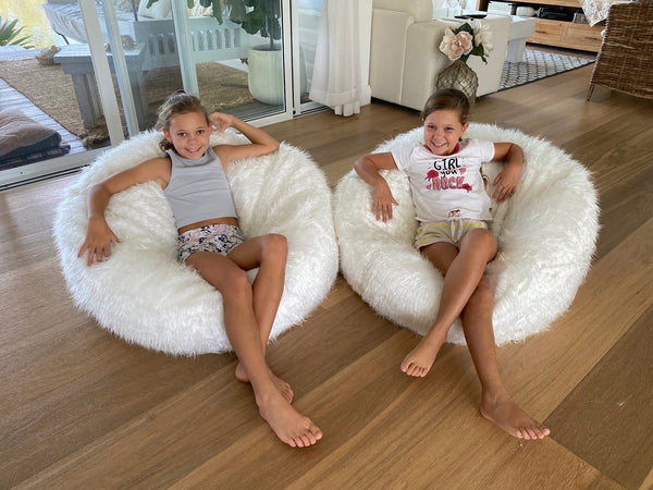 two pretty girls sitting in large white fur bean bags in a living room
