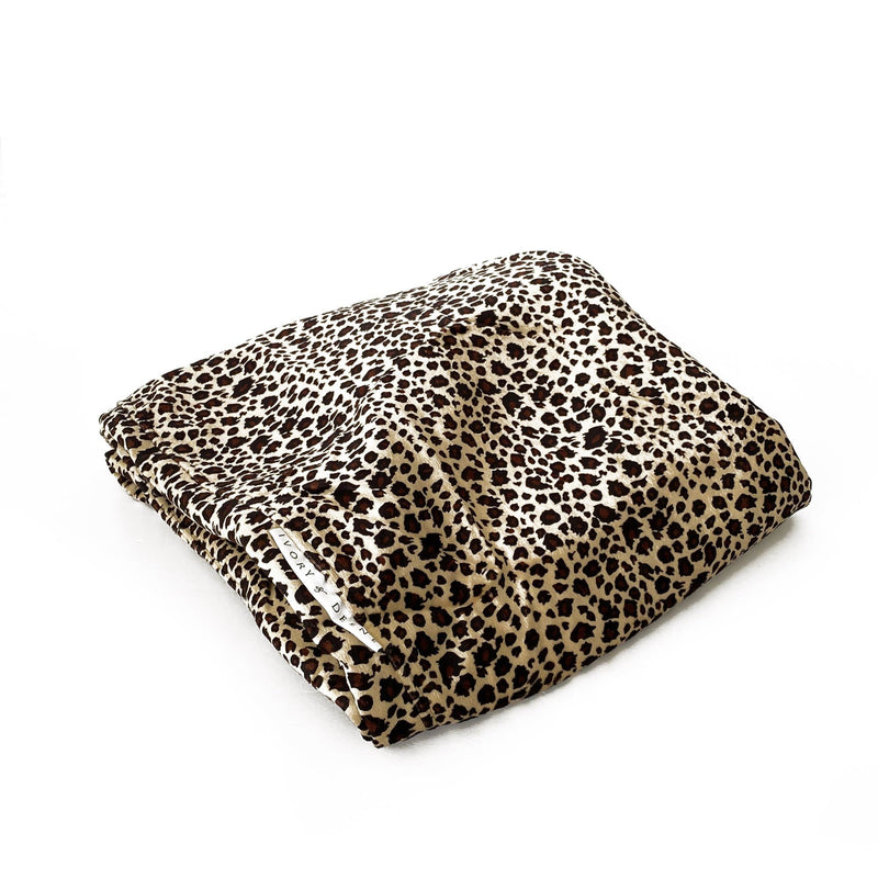 close up of fur leopard beanbag cover on a white background