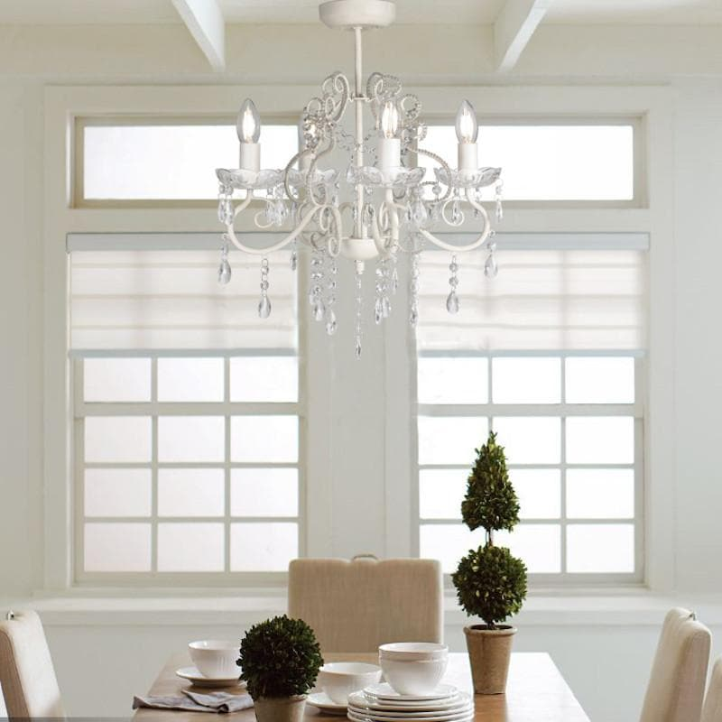 cream chandelier hanging over dining table against french windows