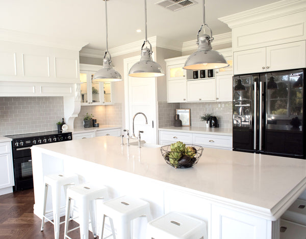 industrial chrome pendant lights in a bright white kitchen with black stove and fridge and white bar stools