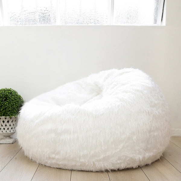 large shaggy white fur beanbag under a warehouse window with a green plant next to it