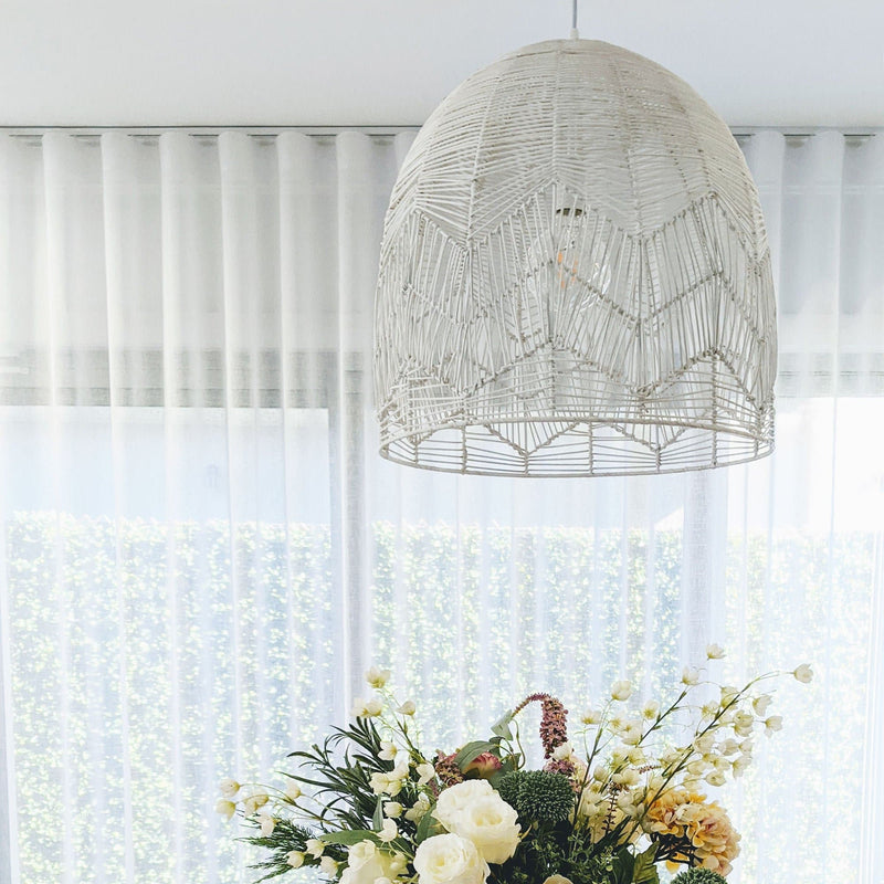 white cane pendant light hanging above fresh flowers and in front of a sheer white curtain