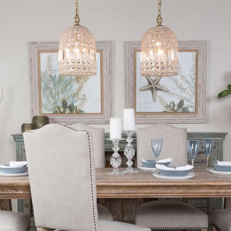 whitney antique brass gold chandelier in a dome shape hanging over a hampton dining table