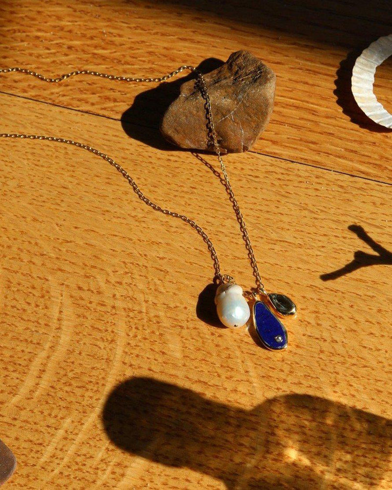 lapis pilar charm necklace on the table