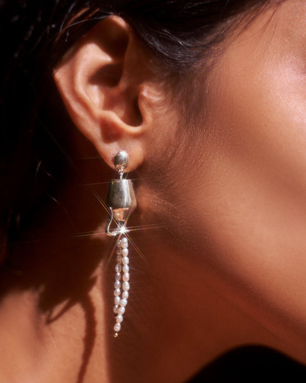 silver vessel drop earrings on the model