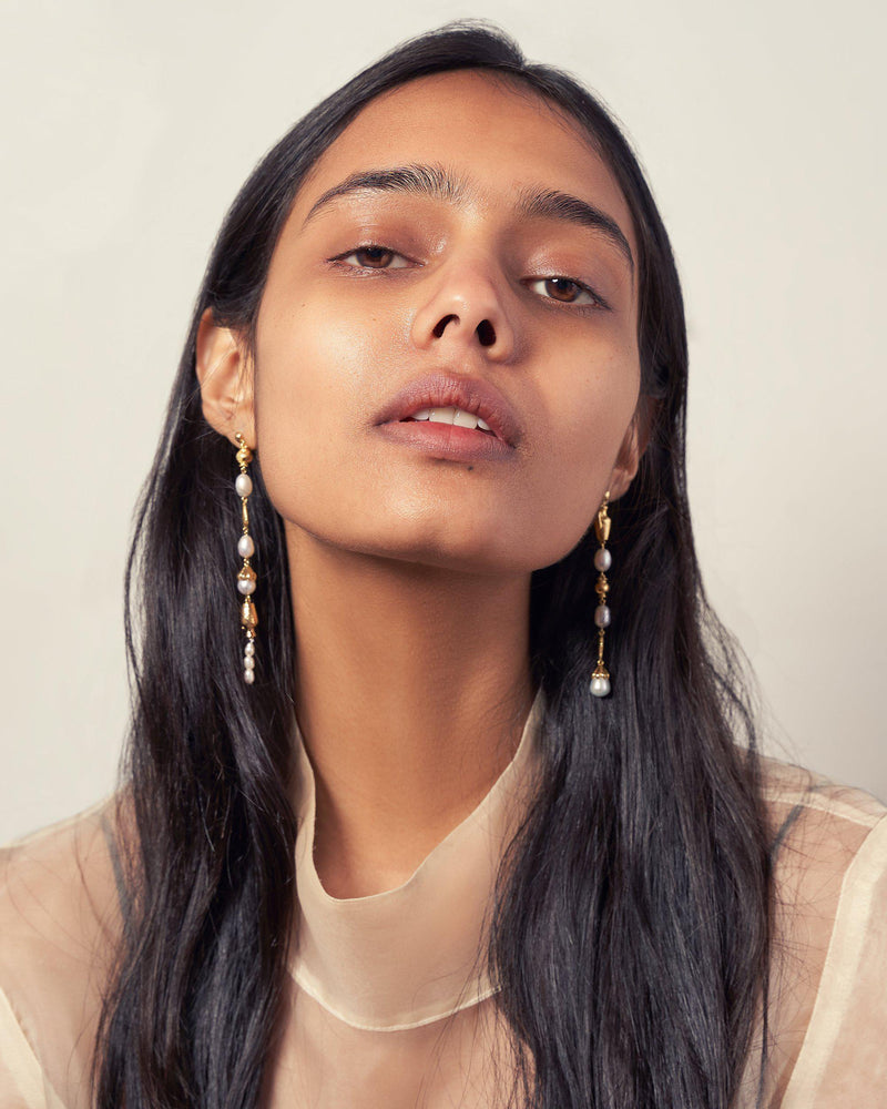 gold pearl drop earrings on the model