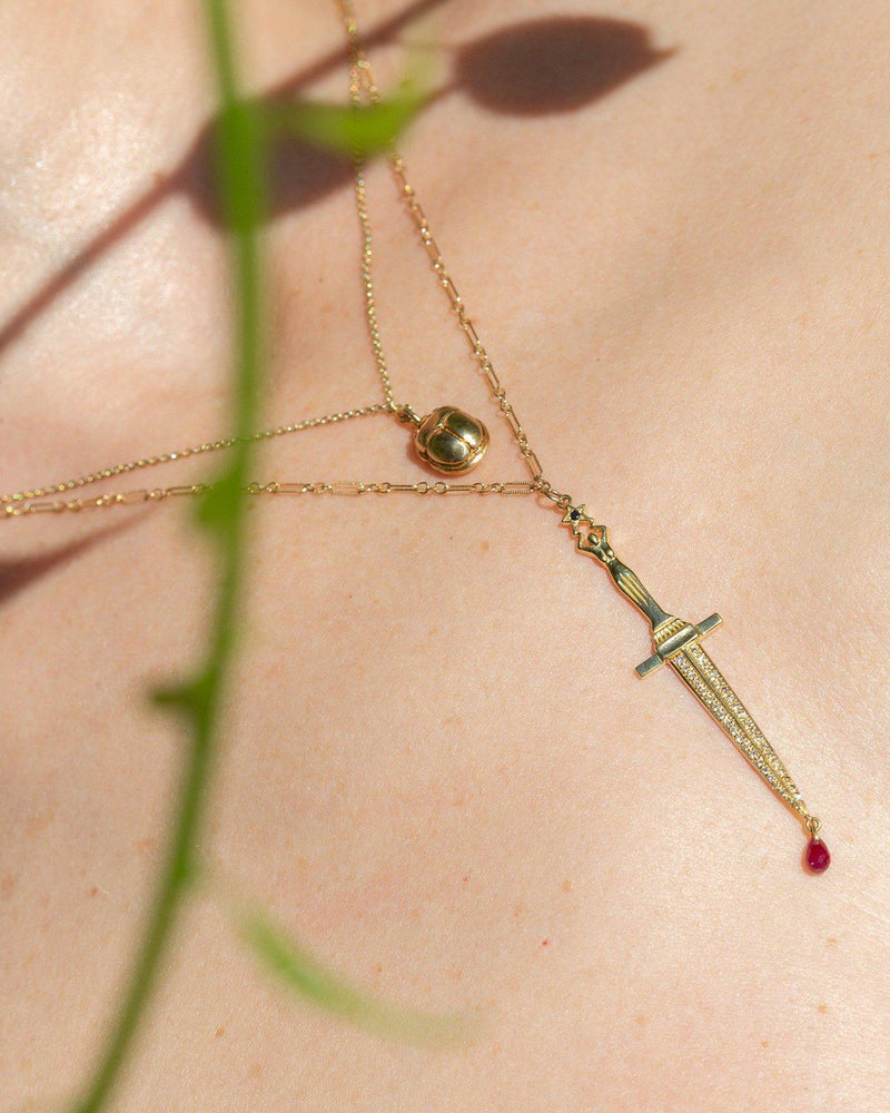 gold dagger pendant with ruby