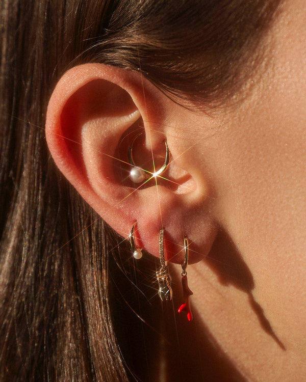 enamel coral branch huggie earring on the model