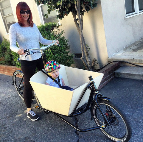 A CETMA cargo bike, mom carrying son in Burbank, CA.