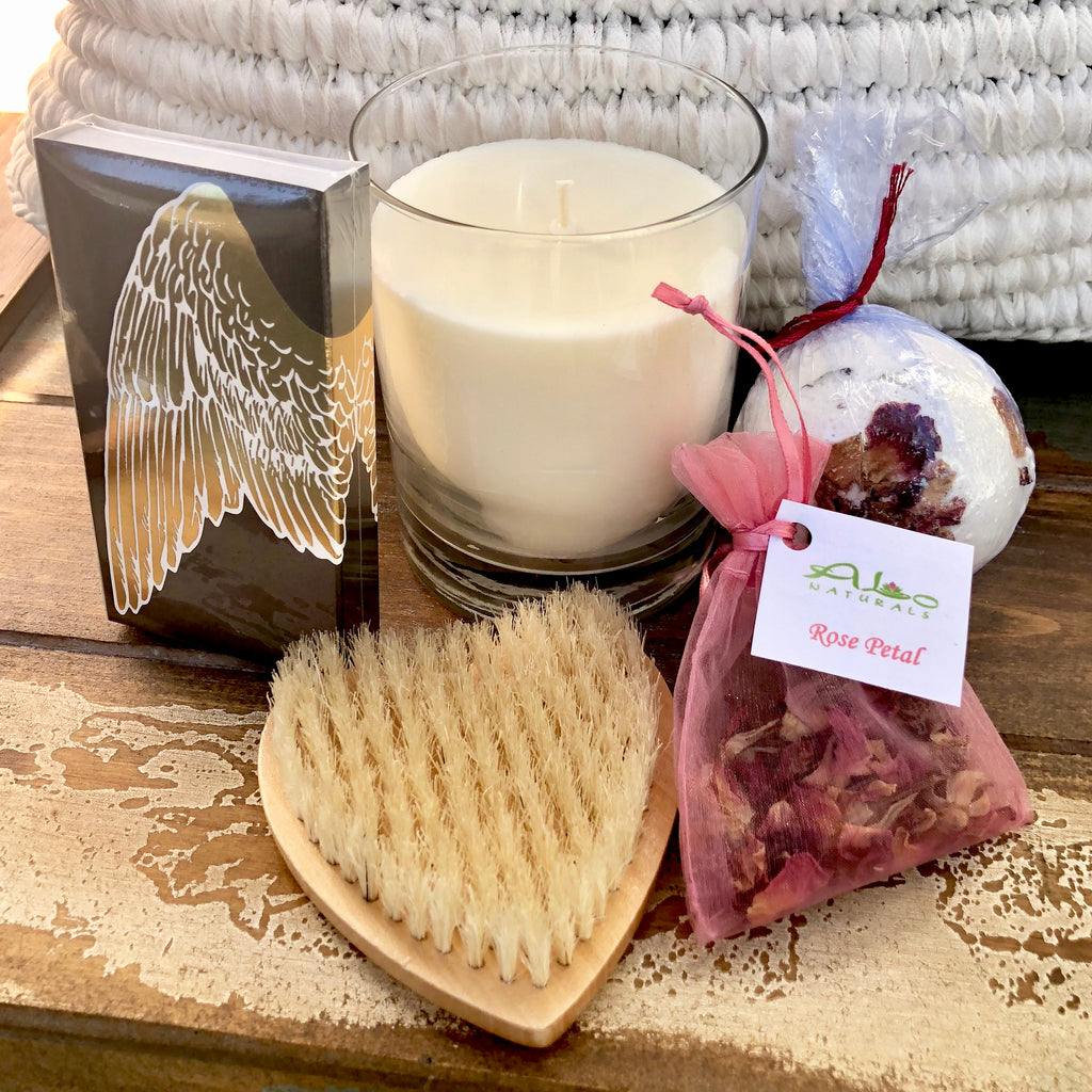 This collection includes a 13.5oz Rose Petal Soy Candle, a box of Angel Wing Jumbo Candle Matches, a Heart Shaped Bath Brush, a Rose Petal Dead Sea Salt Bath Bomb, and a Rose Petal Sachet.