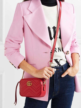 GG Marmont Mini Matelassé Zipped Shoulder Bag In Red holding