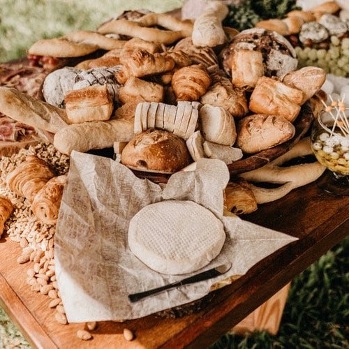Table full of bread and wheel of cheese