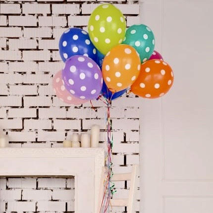 Multi colored polka dot balloons in front of white brick wall