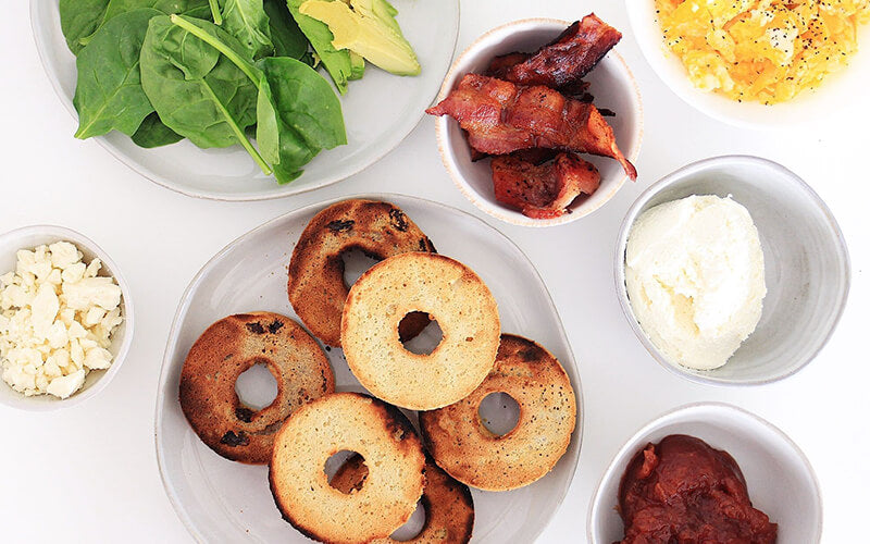 PBH Foods Keto Bagels with dishes of bacon, cheese, eggs, spinach
