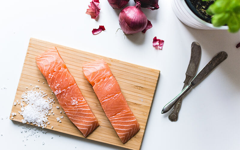 Salmon with salt on wooden board