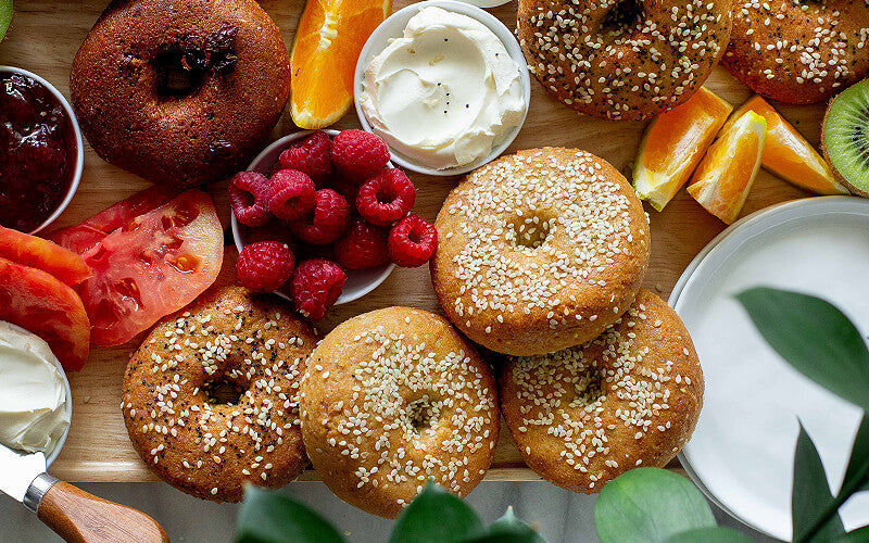 Keto bagels on a tray with assorted fruits and veggies