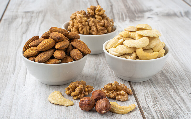 Walnuts, almonds, and cashews in bowls