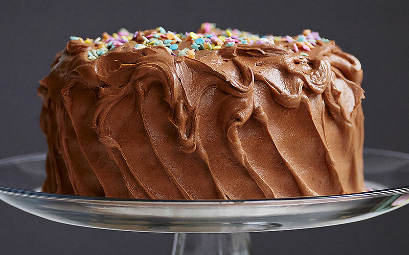 Chocolate frosting on cake with sprinkles on top