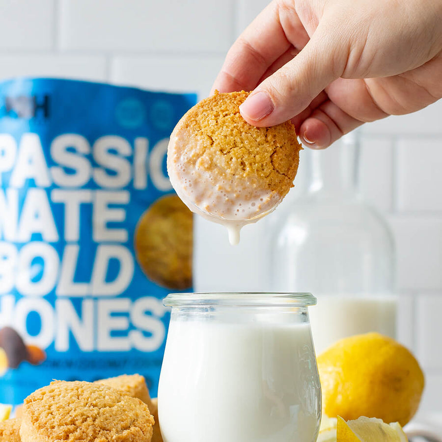 Hand dunking a delicious PBH Foods Keto Lemon Cookie in milk