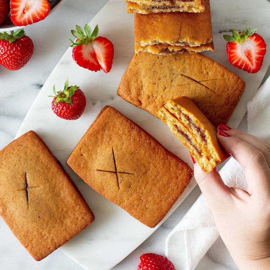 PBH Foods Keto Strawberry Toaster Pastries next to a hand holding a split strawberry pastry